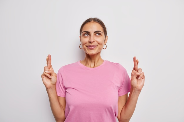 Pleased european woman looks up praying makes wish with fingers crossed waits for miracle waits for important results wears casual pink t shirt isolated over white wall