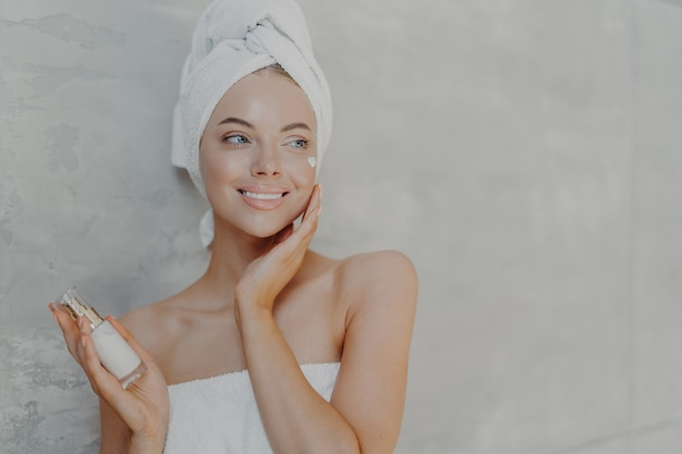 Pleased european woman puts on moisturizing cream on face, looks gladfully aside, touches face, has healthy glowing skin, poses against grey background with copy space for your advertisement Premium Photo