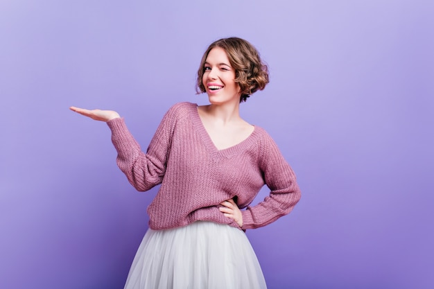 Pleased european woman in trendy white skirt funny posing  attractive caucasian female model with short curly hair standing on purple wall in stylish sweater.
