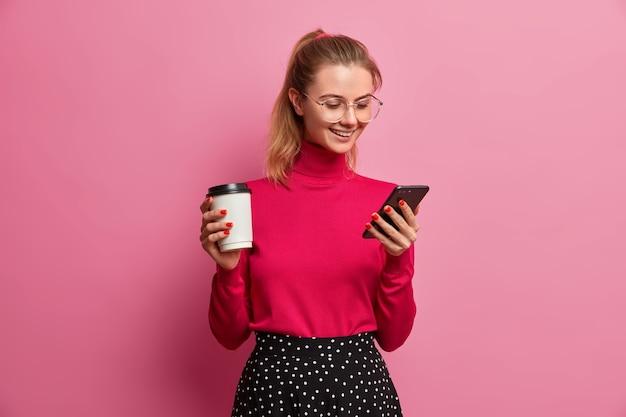 ポニーテールの満足しているヨーロッパの女性はスマートフォンで素晴らしいアプリケーションを楽しんでいます