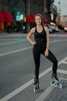 Pleased eurpean woman keeps hand on waist smiles pleasantly leads active lifestyle rides rollerskates dressed in black clothing poses against blurred busy city background. extreme sport concept