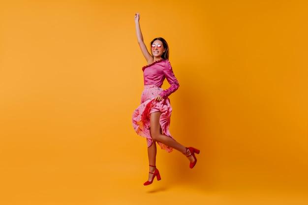 꾸준한 도시 뒤꿈치를 가진 신발을 신은 기쁘고 흥분된 여성이 연 분홍색 실크 옷을 입고 점프합니다. 오렌지 방에서 움직이는 부드럽고 부드러운 머리카락을 가진 소녀의 전신 초상화