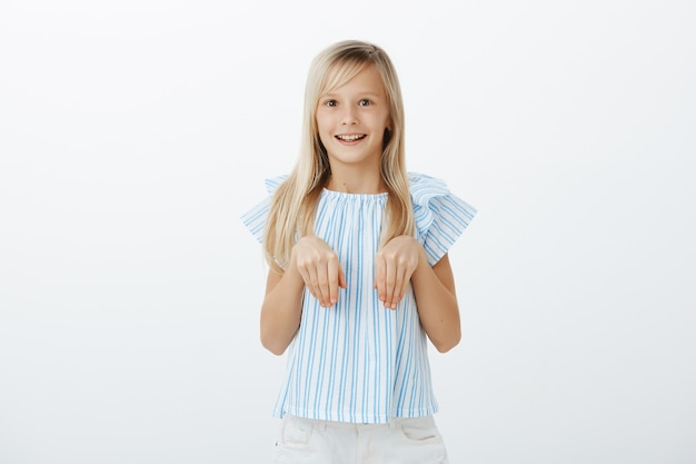 Pleased excited little female child with blond hair in trendy blue blouse holding palms over chest as if it is bunny paws, smiling broadly, feeling amazed while playing with rest of kids on playground