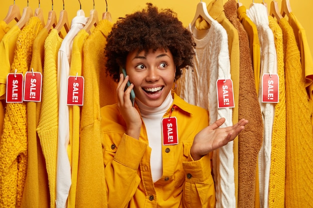 Довольная покупательница разговаривает по телефону с подругой, спрашивает совета, что лучше купить, выбирает одежду в магазине одежды, любит делать покупки, держит ладонь поднятой. концепция розничной торговли.