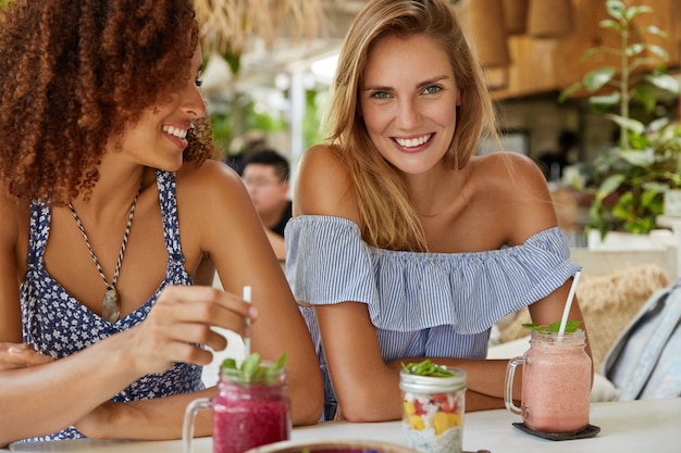 Pleased female lesbians have date at cafe, drink fresh fruit cocktails, discuss something with cheerful expressions, happy to communicate. pretty women spend free time in restaurant together