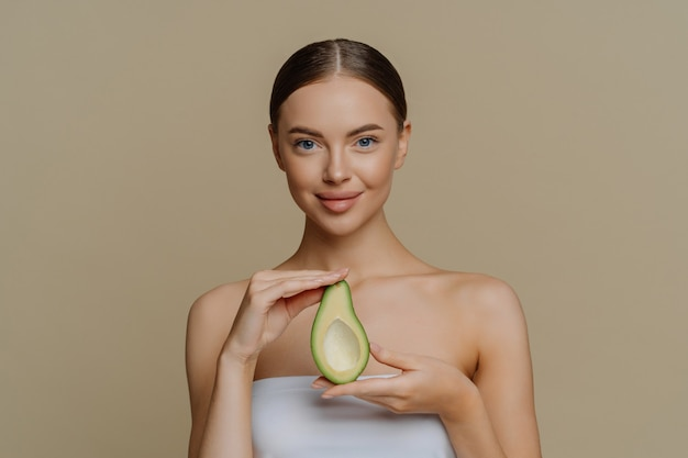 Pleased female model holds half of avocado wrapped in bath towel going to use beauty product