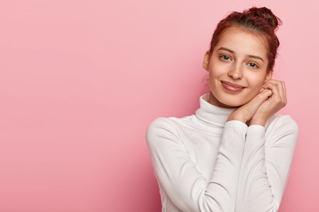 Pleased female model tilts head and smiles gently, keeps palms pressed together near face, has no makeup, wears white turtleneck, looks directly at camera with blue eyes, isolated over pink background