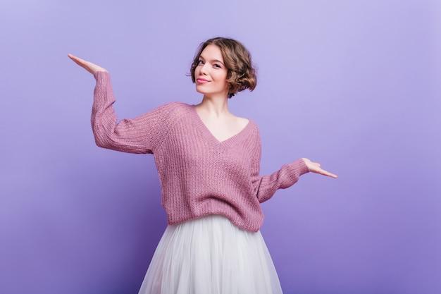 Modello femminile soddisfatto con l'espressione del viso felice in posa in abiti invernali e sorridente. donna dai capelli corti in sciarpa che esprime emozioni positive sulla parete viola.