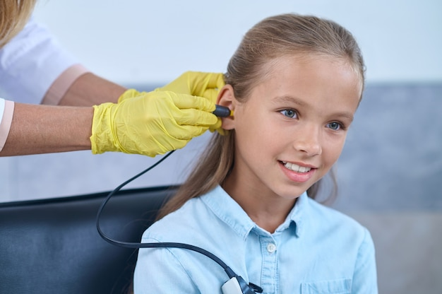 Довольная женщина-пациентка проходит аудиометрический тест