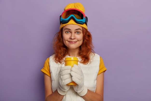 Довольная лыжница имеет перерыв на кофе, носит белые варежки, футболку, желтую шляпу и защитные очки для сноубординга, улыбается с ямочками на щеках, изолированными на фиолетовом фоне.