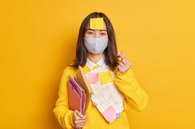 La studentessa soddisfatta indossa una maschera protettiva per prevenire virus e contrarre malattie ha documenti con le informazioni necessarie scritte attaccate sui vestiti fa un segno coreano.