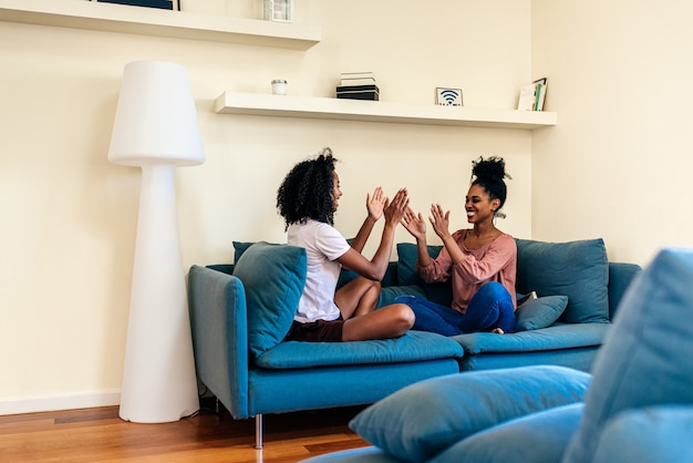 Pleased females playing had clap game on sofa