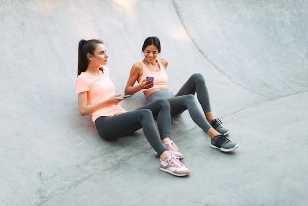 콘크리트 운동장에 앉아있는 동안 미소하고 핸드폰을 함께 들고 운동복에 기쁘게 피트니스 여성
