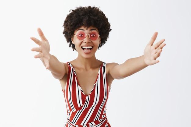 포옹이나 포옹을주는 환영 제스처로 손을 당기는 세련된 안경과 옷을 입은 친절하고 행복한 감정적 인 어두운 피부의 여성을 기쁘게 생각합니다.