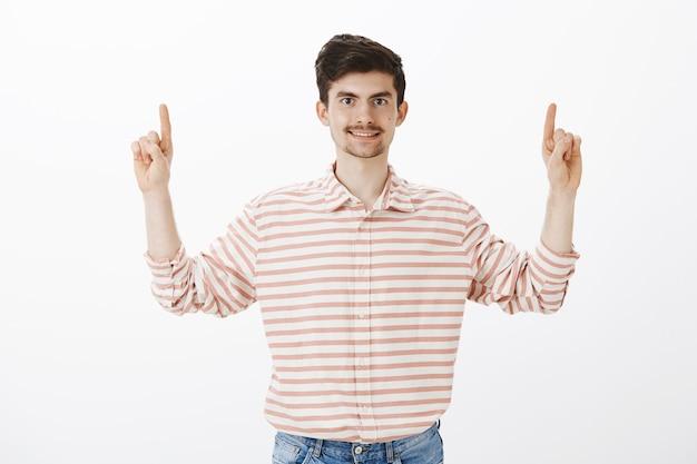 Довольный дружелюбный обыкновенный парень в полосатой рубашке, поднимает указательные пальцы и показывает вверх, широко улыбается, предлагает друзьям сесть в кафе наверху, стоя