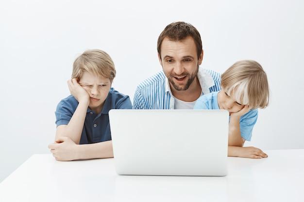 Довольный забавный отец сидит с сыновьями возле ноутбука, смотрит на экран с довольной счастливой улыбкой, а мальчики скучают и равнодушны