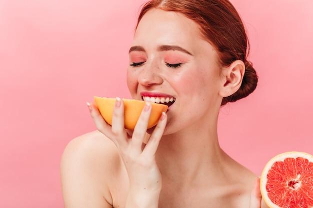 자몽을 먹고 기쁘게 생강 소녀. 분홍색 배경에 과일을 즐기는 관능적 인 여자의 스튜디오 샷.