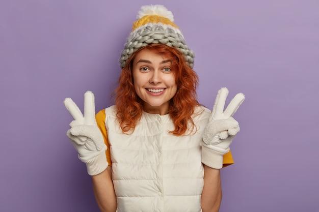 喜んでいる生姜の女性は、気持ちよく微笑んで、手を上げて、平和のジェスチャーをし、冬の帽子、ミトン、白いベストを着て、気分が良く、紫色の背景の上に隔離されています。