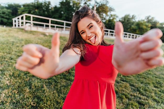 Ragazza soddisfatta in vestito luminoso che balla sull'erba. bella giovane donna in abito rosso in posa nel parco con la lingua fuori.