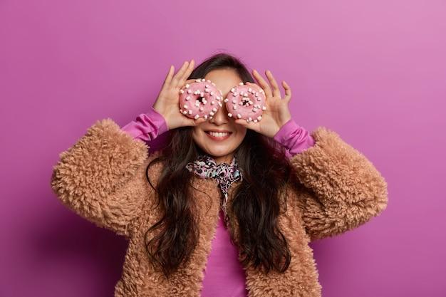 Ragazza soddisfatta tiene due ciambelle dolci sugli occhi, ha un debole per i dolci, sorride ampiamente, vestito con cappotto invernale, mangia cibo malsano