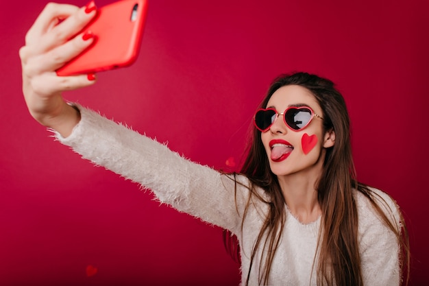 Довольная девушка в забавных очках сердца фотографирует себя