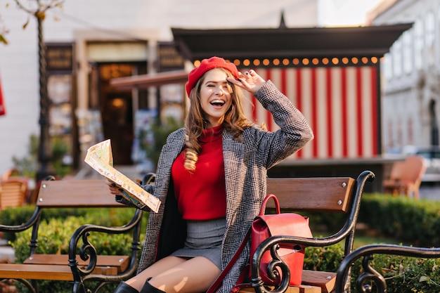 Довольная девушка в короткой юбке сидит на уютной городской площади и смеется