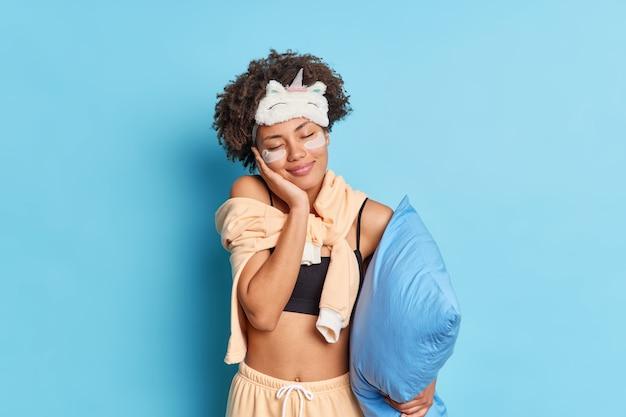 寝間着を着た女の子は、スキンケアの手順で目を閉じた後、顔の柔らかさを楽しんでいます笑顔は青い壁に隔離された枕を心地よく保持しています