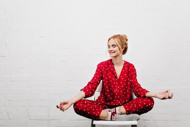 Ragazza soddisfatta in pigiama rosso che fa yoga sulla parete bianca. ritratto dell'interno della giovane signora bionda che si siede nella posa del loto sulla sedia.