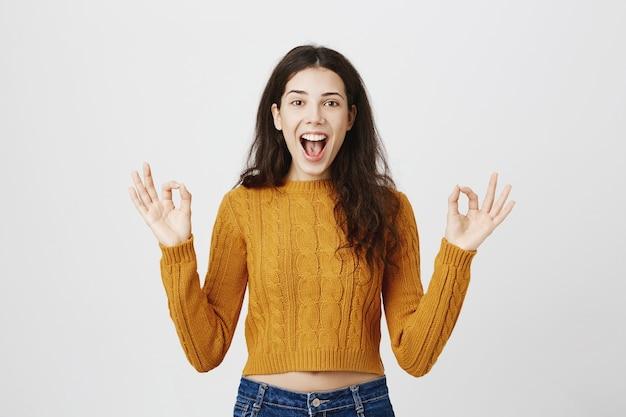 Довольная девушка показывает нормальный жест, делает комплимент, рекомендует идеальный магазин или продукт