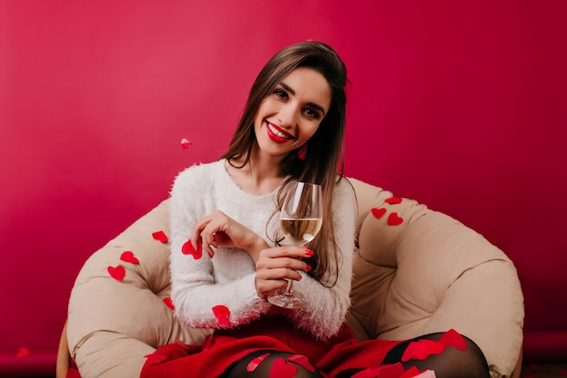 Pleased girl in trendy attire sitting on sofa surrounded by confetti