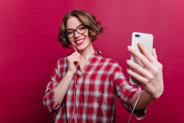 クラレットの壁に自分撮り用の電話を使用して短い髪型の女の子を喜ばせます。巻き毛の自信を持って若い女性の屋内の肖像画は市松模様のシャツを着ています。