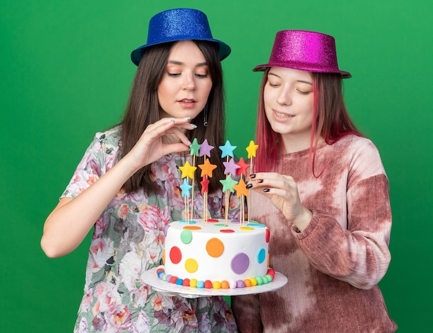 Pleased girls wearing party hat holding and looking at cake isolated on green wall
