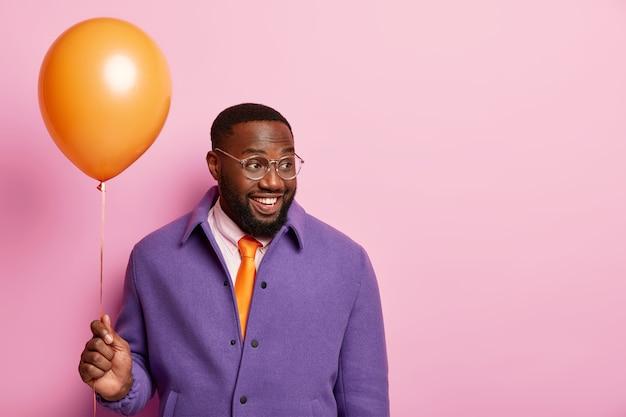 Довольный довольный темнокожий мужчина с густой бородой держит воздушный шар, устраивает вечеринку в офисе, празднует продвижение по службе, радостно смотрит в сторону, одет в праздничную одежду