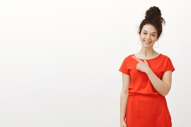左上隅を指し、大きく笑っている赤いドレスを着た見栄えの良い女性らしい女性
