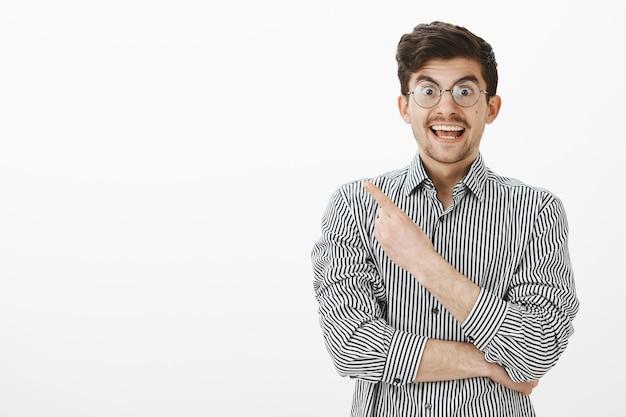 Soddisfatto bell'uomo divertente in camicia a righe che punta all'angolo in alto a sinistra e che sorride ampiamente, essendo eccitato e sorpreso, descrivendo o mostrando cose interessanti e affascinanti sul muro grigio