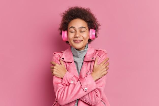 곱슬 머리 아프로 머리를 가진 기쁘게 잘 생긴 소녀는 눈을 감고 음악을 듣고 자신을 포용합니다.