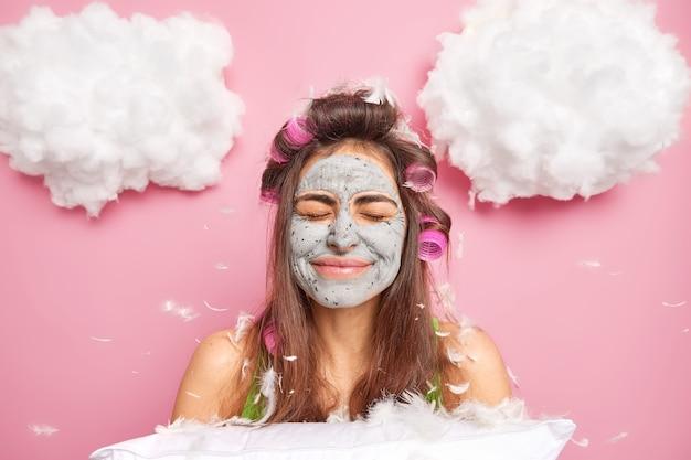 Довольная красивая женщина закрывает глаза улыбается, положительно носит бигуди на голове, позирует с мягкой подушкой, летящие перья вокруг поз на фоне розовой стены