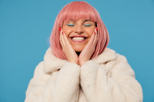 Pleased good looking young cheerful pink haired woman holding her face with raised palms while standing, smiling happily with closed eyes, dressed in fancy clothes
