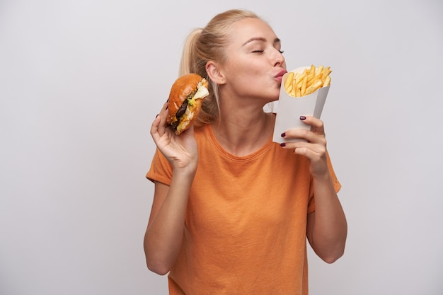 Pleased good looking young lovely blonde female in casual clothes standing over white background with fast food in raised hands, keeping eyes closed while foretasting yummy meal