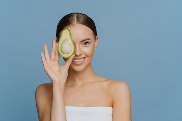 Pleased good looking young woman covers eye with half of avocado enjoys skin care