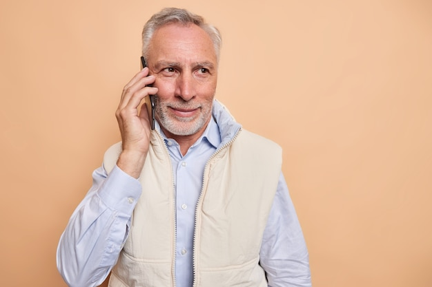 Pleased grey haired man concentrated into distance has telephone conversation