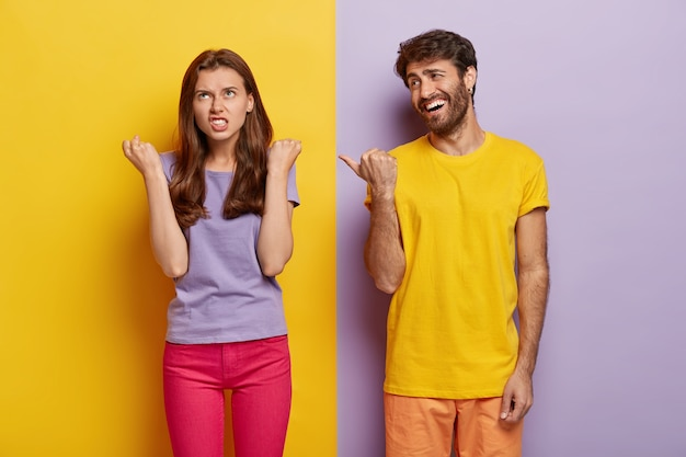 Pleased guy has fun, wears bright yellow t shirt, points thumb at irritated girlfriend who clenches fists with anger