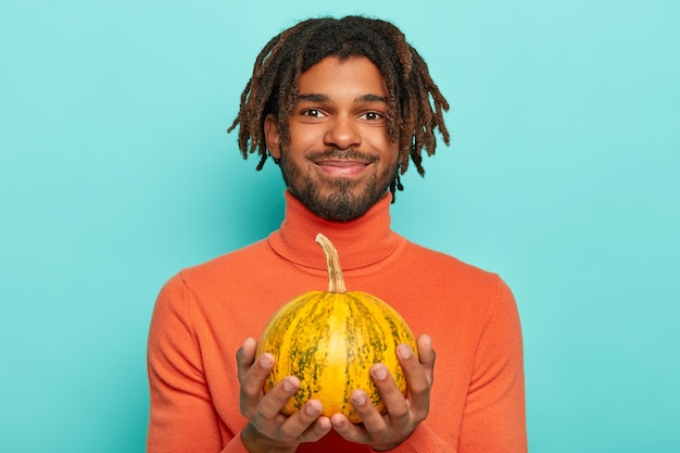 Pleased guy wih dreads holds little pumpkin, going to carve on halloween party, has beard and mustache, wears comfortable poloneck