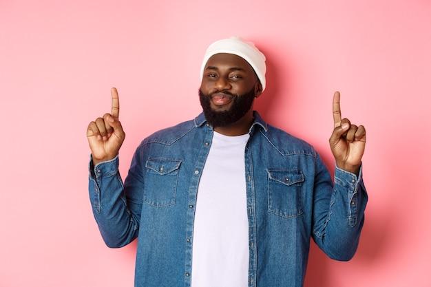 Un bell'uomo di colore compiaciuto che annuisce in segno di approvazione e controlla una buona promozione, puntando il dito in alto all'offerta, mostrando il miglior affare, sfondo rosa.