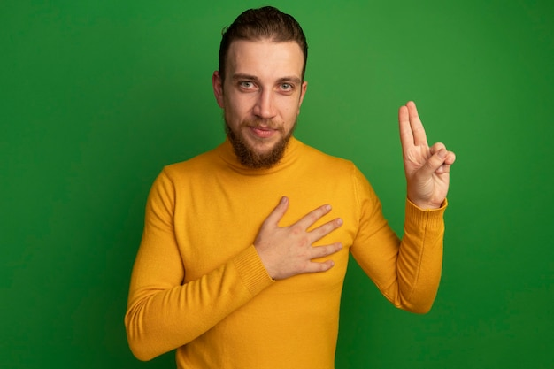 Pleased handsome blonde man doing oath gesture isolated on green wall