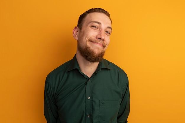 オレンジ色のカメラを見て喜んでハンサムなブロンドの男