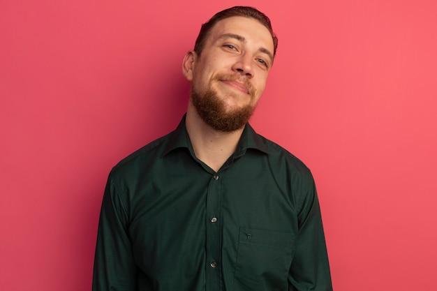 기쁘게 잘 생긴 금발의 남자는 분홍색 벽에 고립 된 앞을 본다