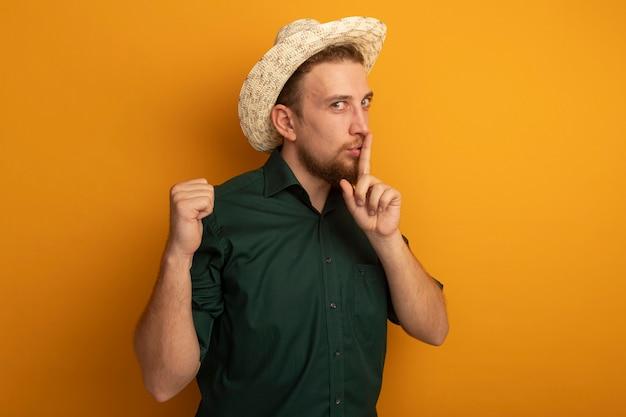 沈黙のジェスチャーをし、オレンジ色の壁に拳を隔離しておくビーチ帽子を持つハンサムなブロンドの男を喜ばせる