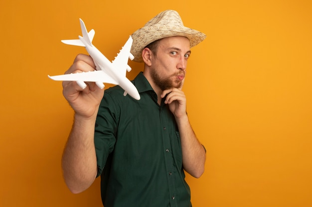 Pleased handsome blonde man with beach hat puts finger on face and holds model plane on orange