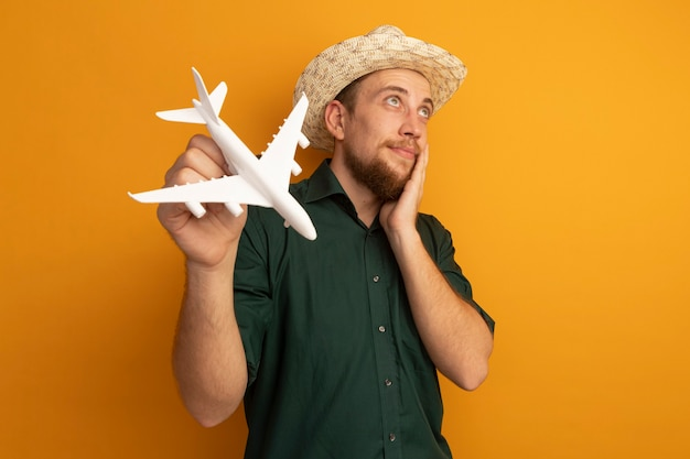 Pleased handsome blonde man with beach hat puts hand on face and holds model plane isolated on orange wall